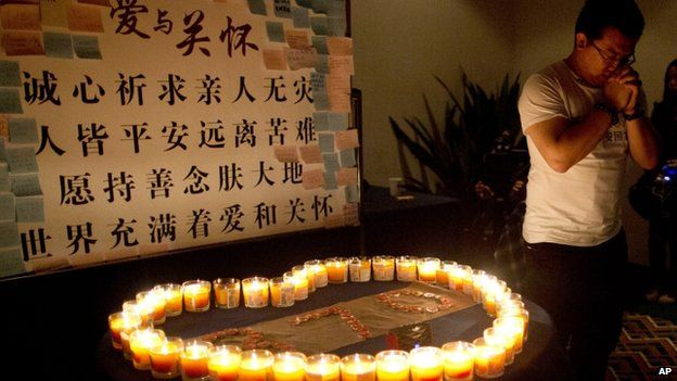 A man, one of the relatives of Chinese passengers onboard Malaysia Airlines Flight 370, prays near candles before a briefing with Malaysian officials at a hotel in Beijing, China, on 31 March 2014