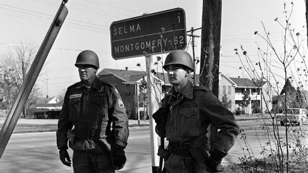 National Guardsmen stand under a road sign showing the distance to the capital - 20 March 1965