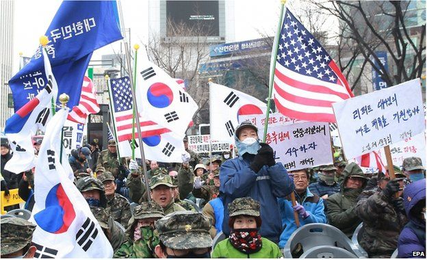 South Korean conservative protesters hold South Korean and US flags to pray for US Ambassador to South Korea Mark Lippert near the US embassy in Seoul, South Korea, 9 March 2015.