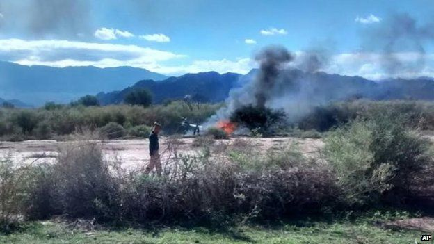 A man stands near the smoking remains of a helicopter that crashed with another near Villa Castelli in the La Rioja province of Argentina on Monday