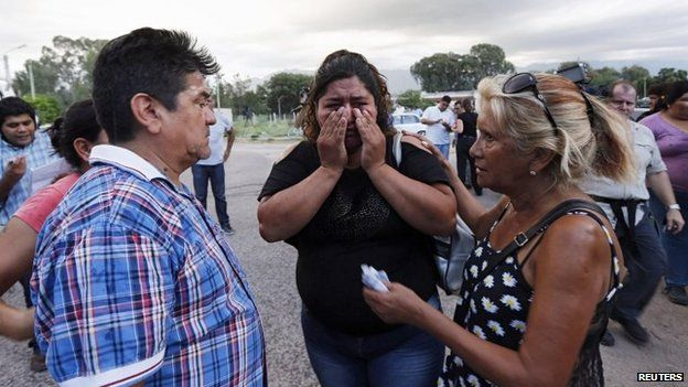 Azucena Aguero (centre), fiancee of pilot Juan Carlos Castillo, who was killed in a helicopter crash, is consoled by a friend outside the judicial morgue in La Rioja on 10 March, 2015
