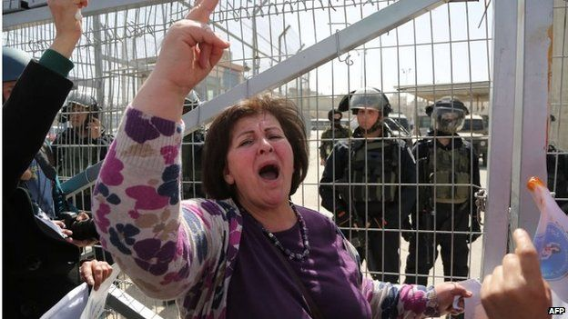 Palestinian woman shouts in front of Israeli soldiers at Qalandiya checkpoint between Jerusalem and Ramallah (07/03/15)