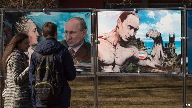 A couple stand next to paintings depicting Vladimir Putin in Crimea (16 March 2015)