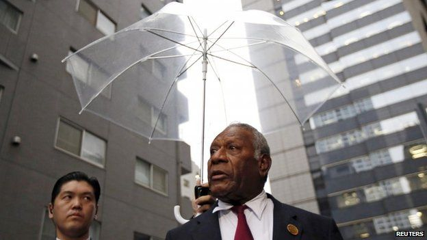 """Vanuatu""""s President Baldwin Lonsdale (R), flanked by a Japanese security police officer holding an umbrella, speaks in Tokyo - March 16, 2015"""