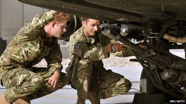 An Apache helicopter is examined by Prince Harry at Camp Bastion in 2012