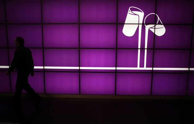 An employee walks past a purple wall with the Cadbury logo of two glasses pouring milk on it. At the company's Bournville production plant.