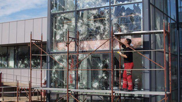 Worker repairs broken windows in Kosovo's capital Pristina, March 2015