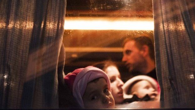 A Kosovo Albanian child and his family sit on a bus heading to Serbia, in Pristina in February 2015, hoping to reach the European Union and seek asylum