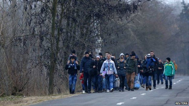 Kosovan migrants walk on a road after illegally crossing the Hungarian-Serbian border near the village of Asotthalom February 5 2015
