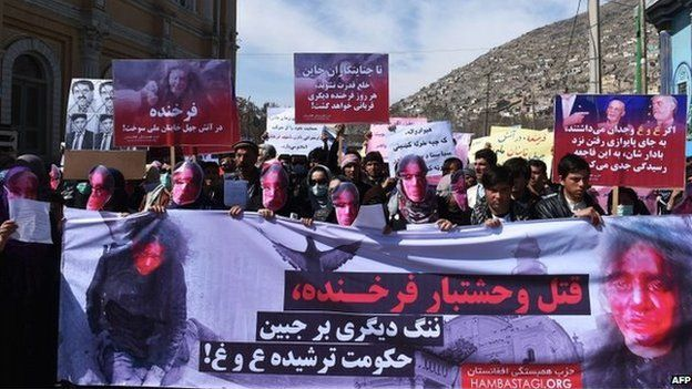 Afghan members of the Solidarity Party of Afghanistan wearing masks bearing an impression of the bloodied face of a woman who was lynched by a mob chant slogans during a protest against the attack in Kabul on March 23, 2015.