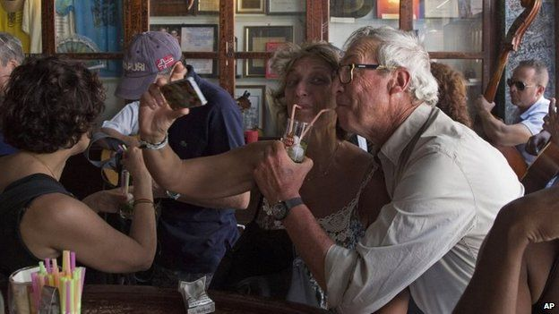 Tourists pose for a photo while sipping on a cocktail at the Bodeguita del Medio Bar in Havana on 22 March, 2015.