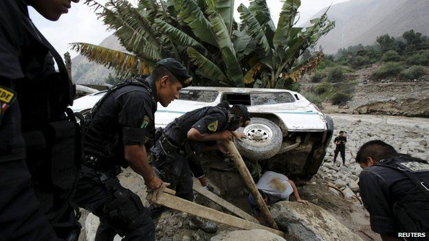 Peruvian police try to remove a car that was stuck in the mud and stones after a landslide in Chosica 24/03/15