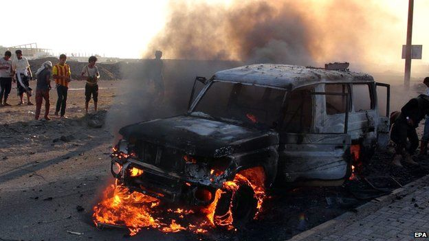 Yemenis gather beside a burning vehicle allegedly belonged to Houthi fighters following clashes with tribal militiamen loyal to Yemeni president Hadi in the southern port city of Aden on 26 March, 2015.