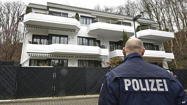 A police officer stands in front of an apartment building where they believe Andreas Lubitz, the co-pilot of the crashed Germanwings airliner jet, lived on 26 March, 2015,