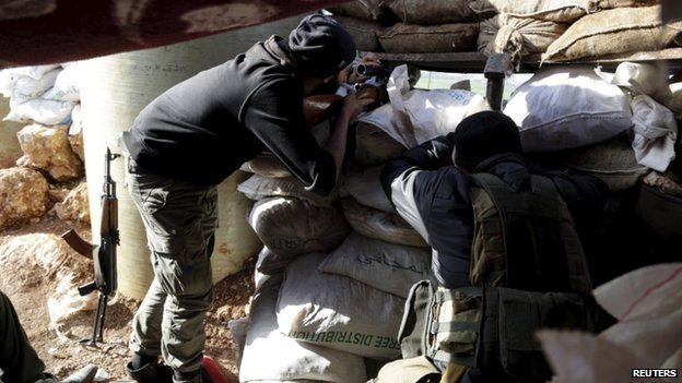 Ahrar al-Sham Islamic Movement rebel fighters stand behind sandbags with their weapons in the north-western city of Idlib 26 March 2015