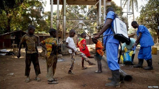 Children come forward to get their feet disinfected in Guinea