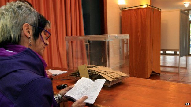 Marie Buck, an councillor, reads a book at a polling station during the first round of local elections, 22 March 2015,