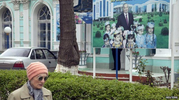 """A woman walks past an election board of Uzbekistan""""s President and presidential candidate Islam Karimov near a polling station in Tashkent March 29, 2015"""