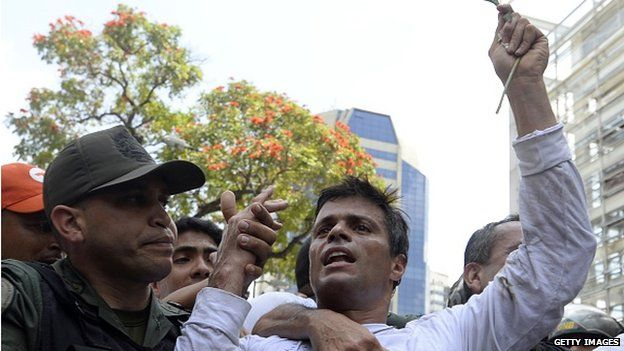 Leopoldo Lopez is escorted by the national guard after he turned himself in on 18 February, 2014.