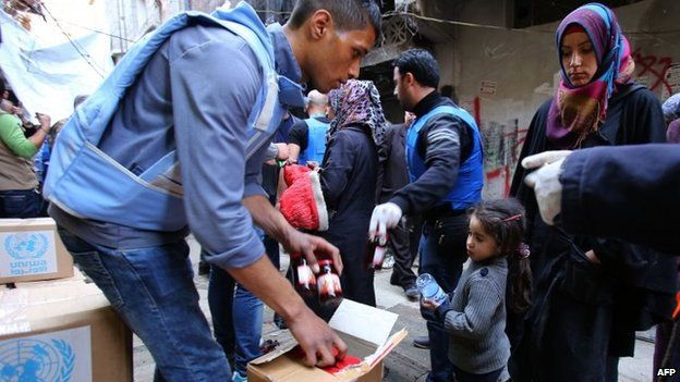 Palestinian refugees receive aid items distributed by the United Nations Relief and Works Agency for Palestine Refugees (UNRWA) at the Yarmouk refuge camp, south of Damascus, 10 March 2015
