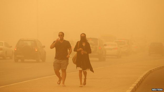 A woman walks with her face covered during a sand storm in Dubai 02 April 2015.