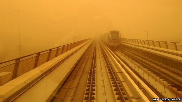 A Dubai metro train is seen driving amid a sandstorm that engulfed the city on 02 April 2015