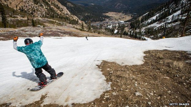 A snowboarder threads his way through patches of dirt at Squaw Valley Ski Resort, March 21, 2015 in Olympic Valley, California.