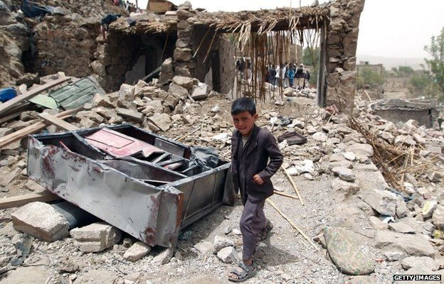 A Yemeni boy walks past the rubble of destroyed houses in the village of Bani Matar, 70 kilometers (43 miles) West of Sanaa, on 4 April, 2015