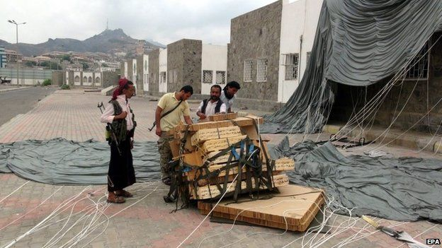 Tribal militiamen loyal to Yemeni President Abdo Rabbo Mansour Hadi collect boxes full of weapons allegedly dropped by the Saudi-led coalition in Aden