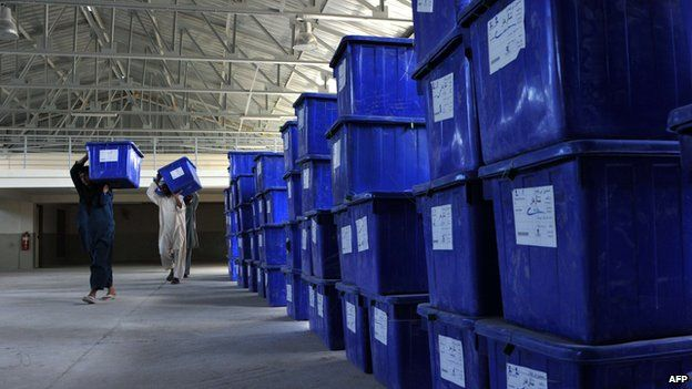 Afghan election commission workers carry plastic ballot boxes at a warehouse in Jalalabad on 12 June, 2014