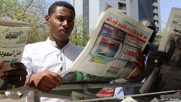 Sudanese men look at newspapers displayed at a kiosk in the capital Khartoum