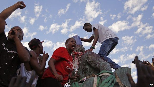 Students shout out and place a bucket on the head as they climb on top of the decades old bronze statue of British colonialist Cecil John Rhodes, as the statue is removed from the campus at the Cape Town University