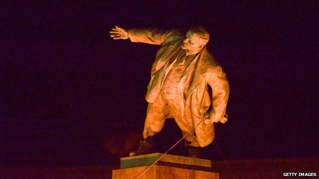 A statue of Lenin being toppled