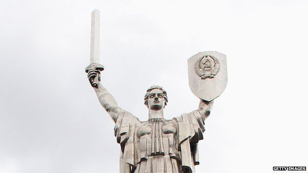 Motherland statue in Kiev, with a Soviet coat of arms on a shield