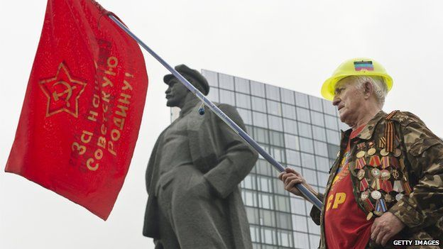 Man with a red flag standing next to a statue of Lenin