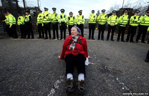 An anti-Trident demonstrator sits in the road at the entrance at the North Gate at HM Naval Base Clyde, Faslane