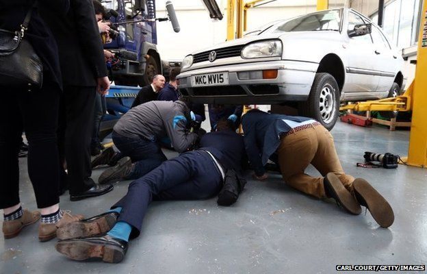 Photographers lie under a car as they photograph Liberal Democrat leader Nick Clegg