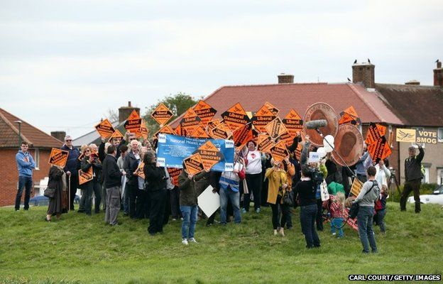 Supporters and protesters await the arrival of Liberal Democrat leader Nick Clegg near St Heliers Hospital in Carshalton