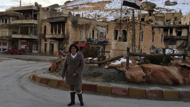 Antoinette Nasrullah in Maaloula, standing in front of wrecked buildings (including her own)