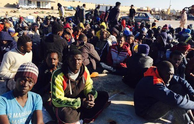 Migrants sit on the ground in Misrata