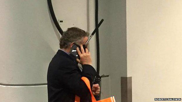 A man takes a call with the selfie stick still attached to his phone