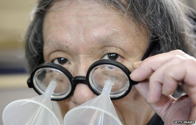 Kenji Kawakami, inventor and founder of the International Chindogu Society demonstrates his funnel glasses designed to guide eye drops so that they never miss their mark.