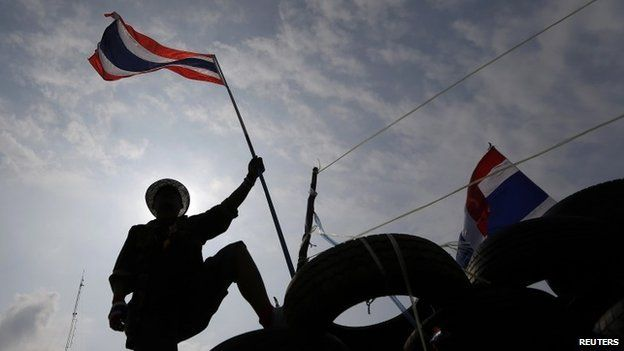 An anti-government protester holds a flag on a barricade as policemen gather in front of it near the Government House in Bangkok 18 February, 2014