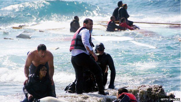 Local residents and rescue workers try to help migrants after their boat sank off the island of Rhodes, Greece