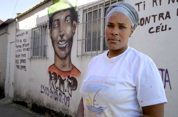 Domingas Sanches next to the picture of her son on a wall