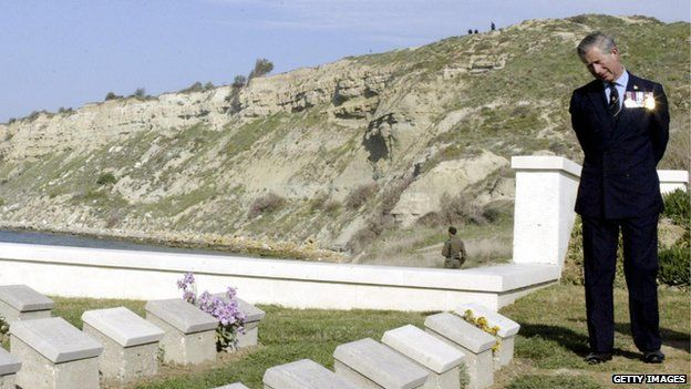 Prince Charles reads the names on graves at the W Beach British Graveyard In Gallipoli while in the background are the cliffs and the beach where the British soldiers died 90 years ago in the Gallipoli peninsula 25 April 2005