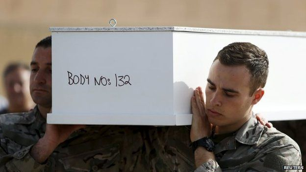 Armed Forces of Malta soldiers carry a coffin with the body of a teenager who drowned in Sunday's disaster