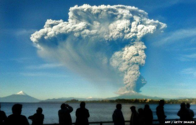 People watch from Puerto Varas, southern Chile, a high column of ash and lava spewing from the Calbuco volcano, 22 April 2015.