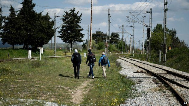 Syrian refugees who have just arrived at the border train station of Idomeni, northern Greece, head for the unguarded border with Macedonia on 21 April 2015