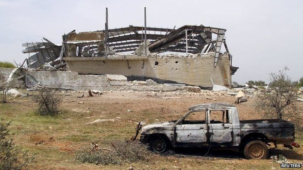 Wrecked building and vehicle at al-Qarmid military base in Idlib province (27 April 2015)